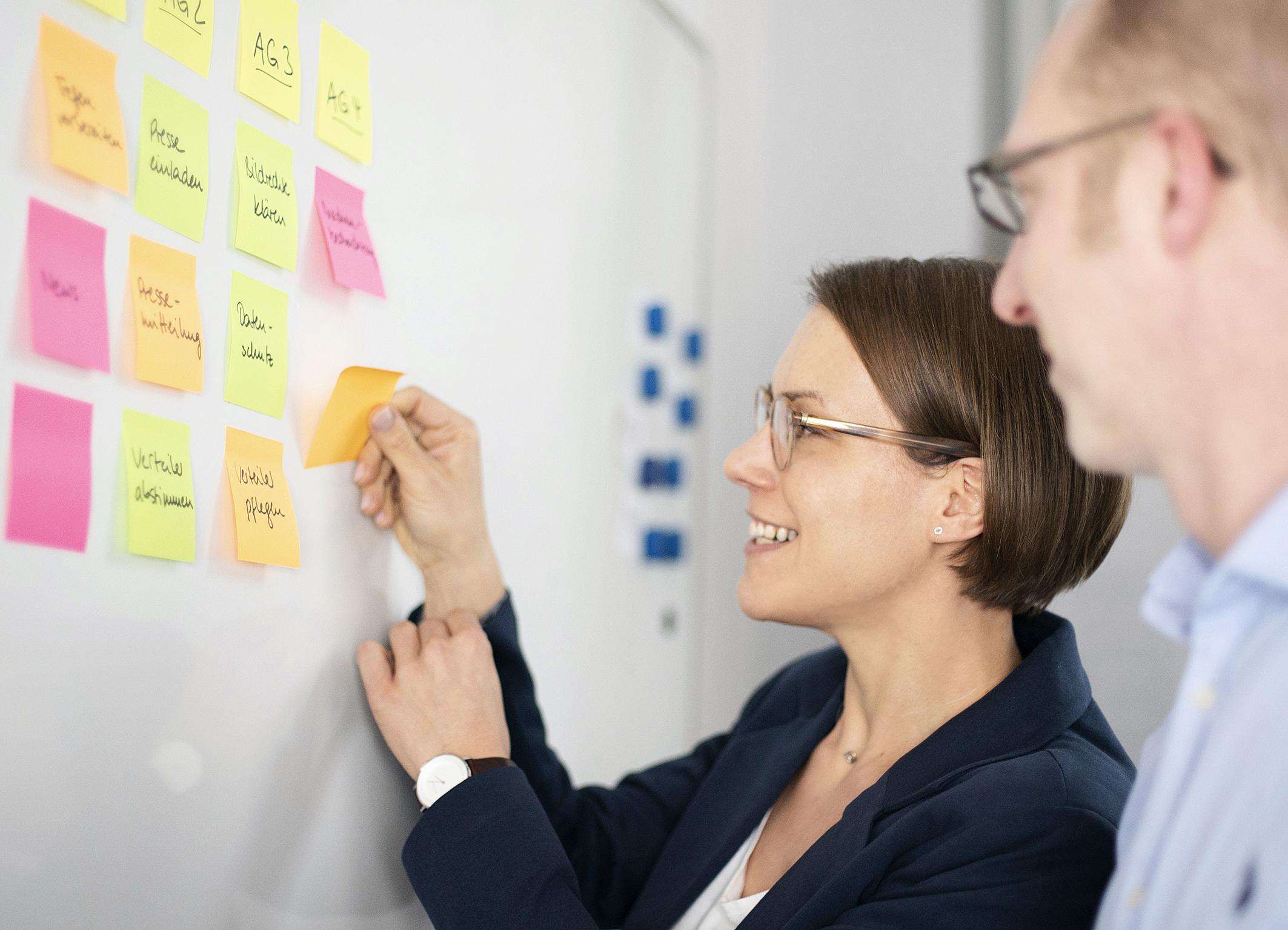 Eine Beraterin und ein Berater stehen am Whiteboard.